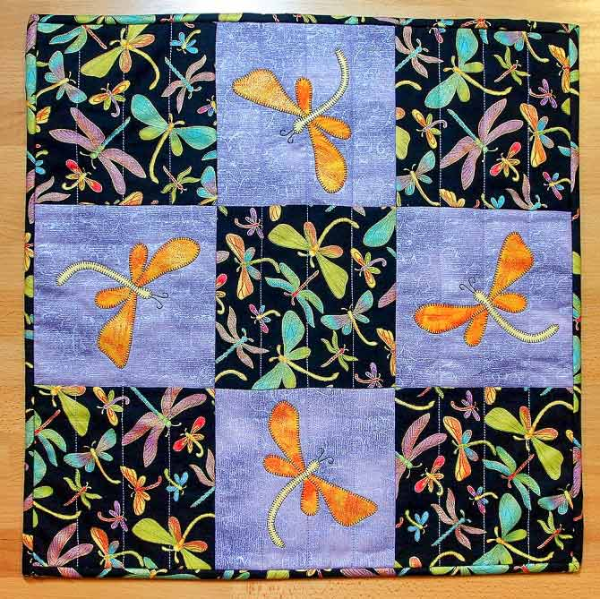 Dragonflies appliqued onto the nine patch dragonfly table topper to match the on-the-go place-mats!