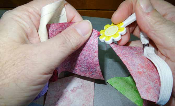 Using thread cutter to cut fabric thread between sewed pieces of fabric on the chain piecing.