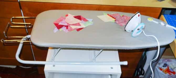 Every seam must be pressed open. I am pressing seams open using a Go Board mini iron on a small ironing board that can be used anywhere.