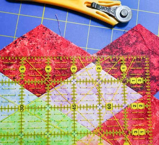 """A ruler is placed on the wall hanging ¼"""" above the points in order to to cut off excess fabrics of the sides."""