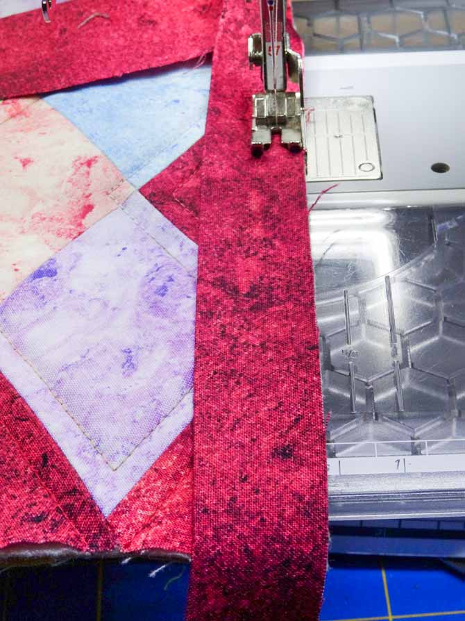"""Binding is on the quilt top. It is being sewed by machine with the seam at ¼"""" form the edge."""