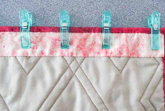 Larger clever clip are considerable larger than the smaller clips. They are being use to keep the sleeve down. This will make it easier to sew the sleeve to the quilt.