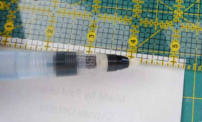Using the Fabric folding pen is being passed on the edge of a ruler leaving a mark that will be use to fold the edges of the label. Clover fabric folding pen