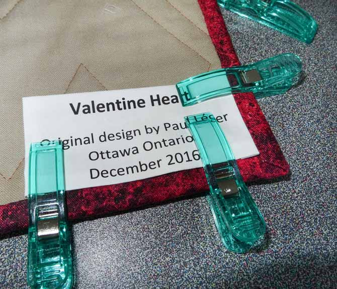 A lable is being held down in place by lage Clever Clips before it is sewn down to the back of the quilt.