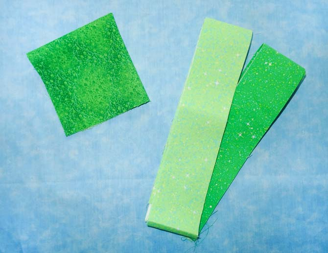 Three pieces of green fabrics that will be used to create the shamrock stained glass quilted wall hanging.
