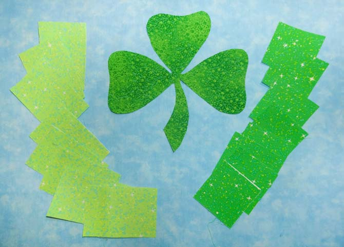 The green fabric pieces and the light blue background fabrics that will be used to make the shamrock stained glass wallhanging using HEATNBOND Lite Iron-On Adhesive Sheets.