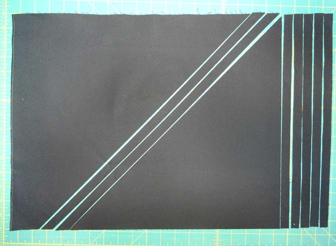 "A rectangle of black fabric showing ⅝"" strips cut on the diagonal and on the straight of grain."