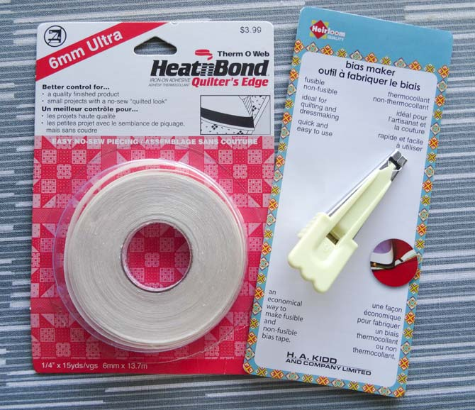 Heirloom bias tape maker and HeatnBond quilter's edge iron-on adhesive tape that will be used to make adhesive bias tape for the stained glass wallhanging.