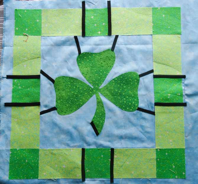 The smallest pieces of bias tape are placed first on the quilt and then ironed into place.