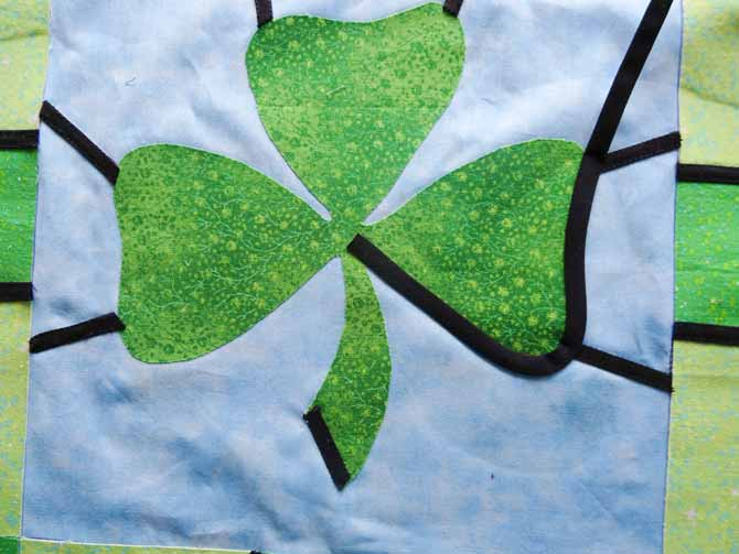 The end of a length of bias tape is placed at the center of the shamrock and then curved along the edge of one of the clover leaves.