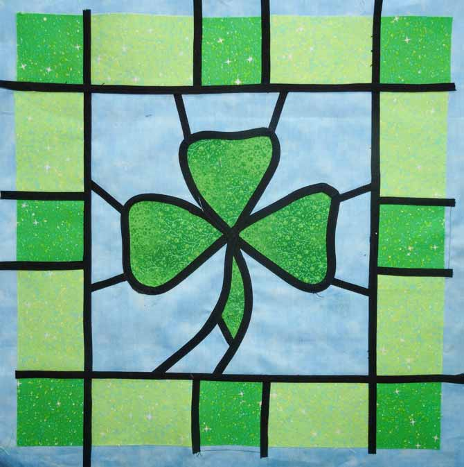 The four remaining lengths of bias tape are place on the inner edges of the four borders of the shamrock wallhanging.