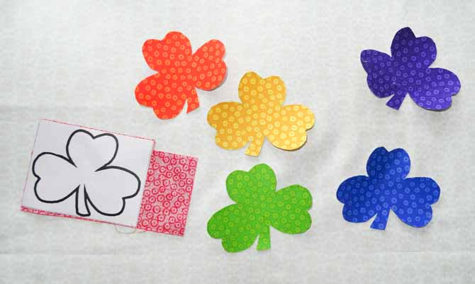 The shamrock designs printed on the HEATNBOND® EZ-Print™ Lite Iron-On Adhesive are fused onto the wrong side of colorful fabric pieces and then cut in the shape of the shamrocks.