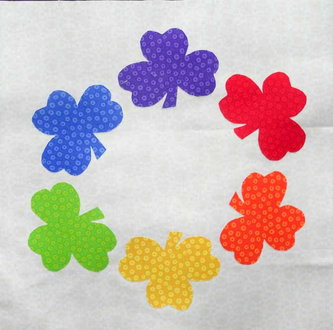 The shamrock applique pieces made with HEATNBOND® EZ-Print™ Lite Iron-On Adhesive are fused onto the background fabric in a circle.