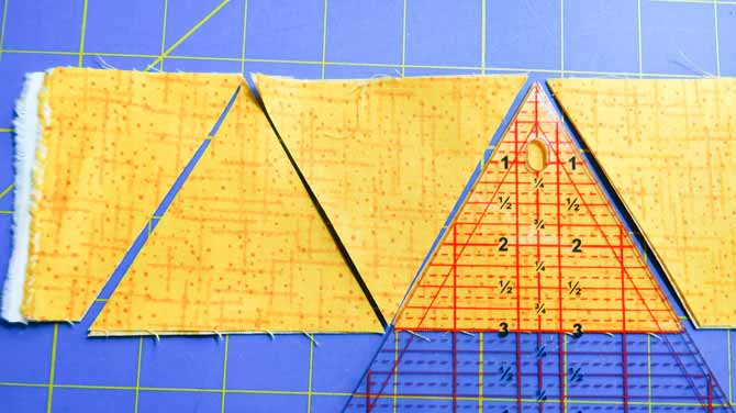 Several triangle pieces can be cut from each strip of fabric by flipping the Sew Easy ruler around from top to bottom.