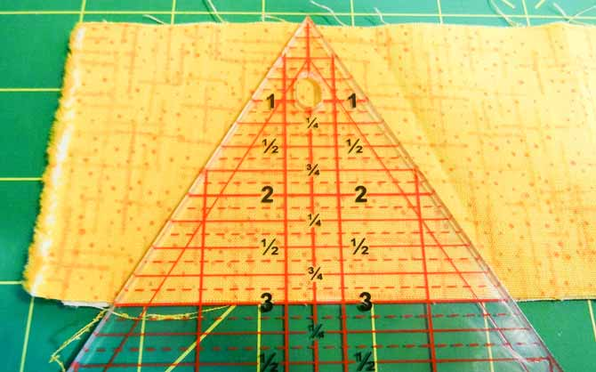 The Sew Easy Triangle ruler was placed along the straight edge of the fabric with the upper point of the ruler touching the upper edge of the strip.