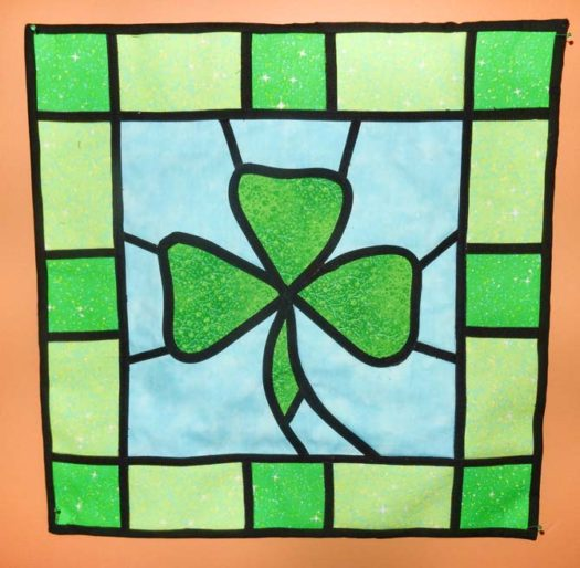 A quilted stained glass wall hanging featuring a green shamrock over a blue background, framed with square and rectangular pieces of complimentary green fabrics. Made with the help of HEATNBOND Iron-On Adhesive Sheets
