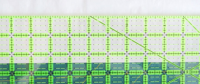 """A ruler is placed over the HEATNBOND® Lite Iron-On Adhesive Sheets showing where it will be cut, just shy of 2½""""."""