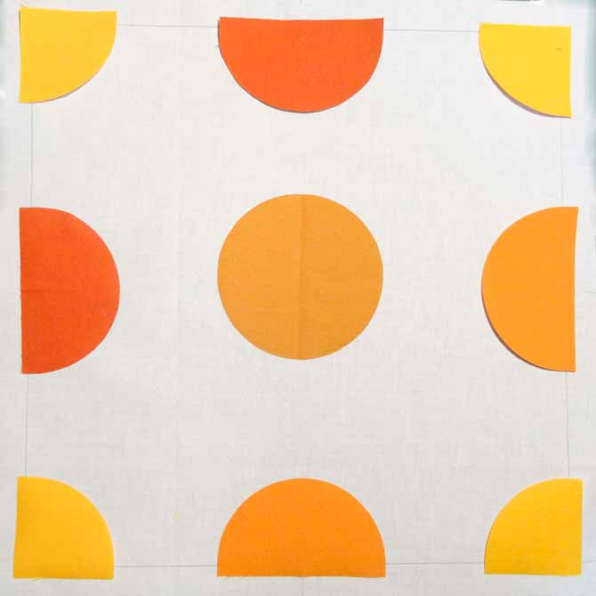 """One full circle placed in the center of a 12"""" quilt block background surrounded by semi circles and quarter circles. Komfort KUT Slash-N-Circle Ruler."""