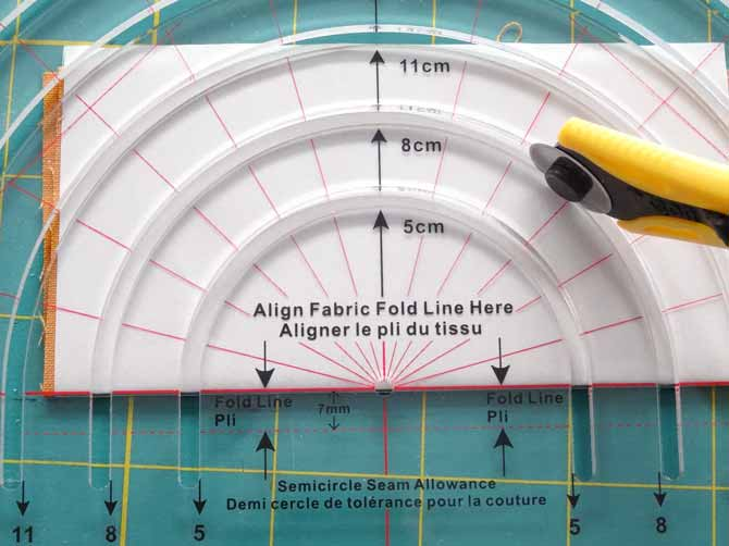The Komfort KUT Slash-N-Circle Ruler on top of a piece of fabric with the rotary cutter on the 8cm curved line.