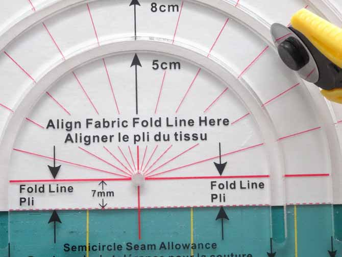 Cutting a semi circle by ensuring the red dotted line is aligned with the bottom of the fabric. Komfort KUT Slash-N-Circle Ruler.