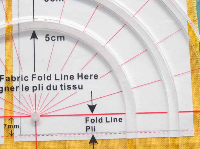 The dotted line of the Komfort KUT Slash-N-Circle Ruler placed on the penciled line of the fabric to cut a quarter circle.