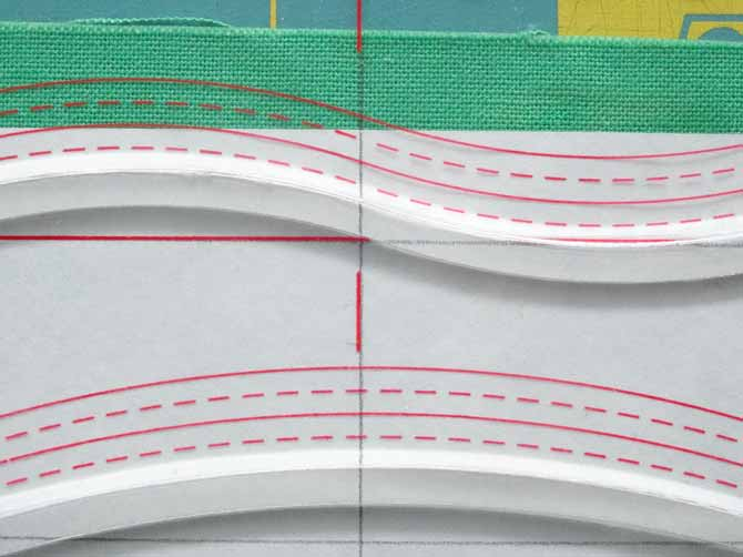 To make a wider curved piece, the lines on the Komfort KUT Slash-N-Circle Ruler are lined up with marked lines in the fabrics.