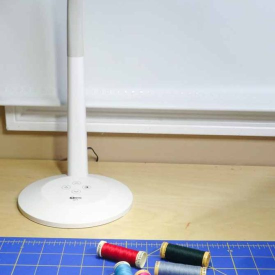 The SURElight M4T LED Desk Lamp on a desk top lighting several spools of coloful threads.
