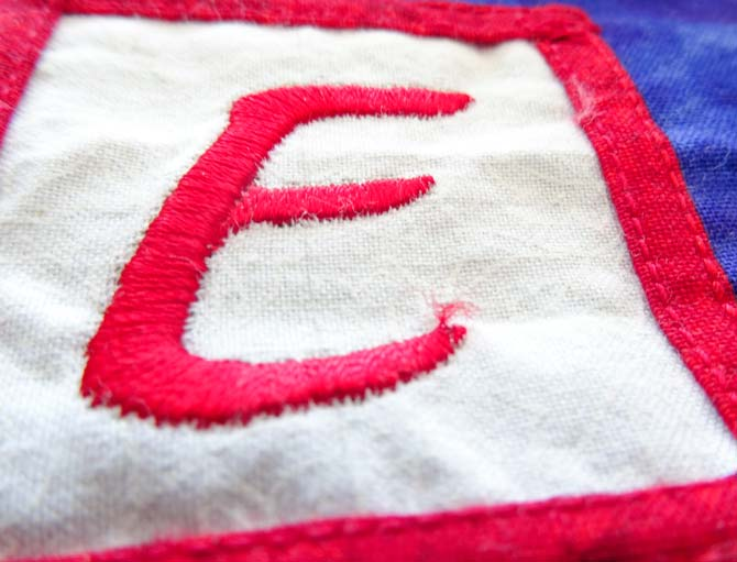 An embroidered letter E is starting to fray. UNIQUE creativ Fray Stop - 2 fl. oz.
