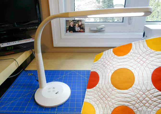 The completed quilted quilt block is shown with the SURElight desk lamp illuminating the quilt top.
