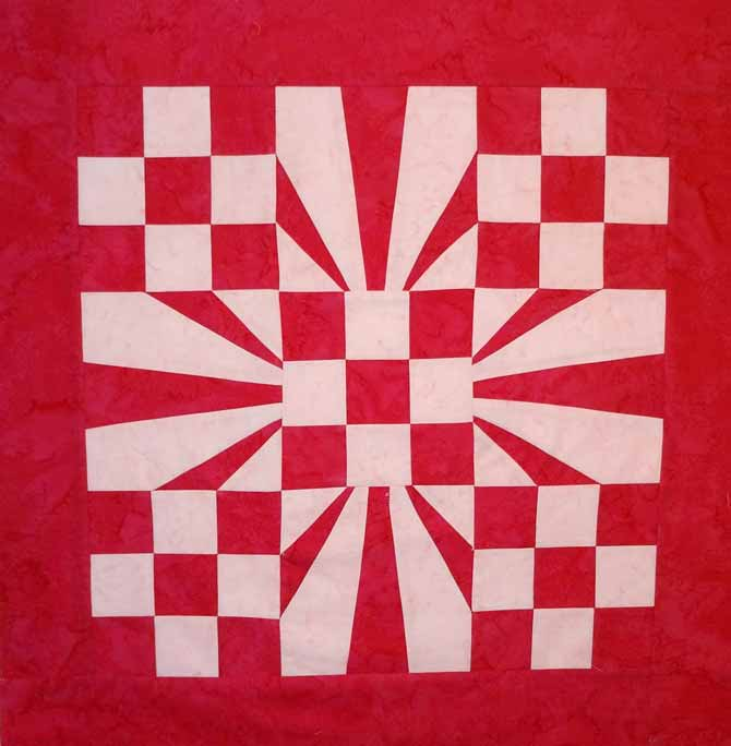 "A red and white quilt top made of 5 nine patch blocks and 4 foundation piecing blocks. The 9 block quilt has a 3"" red border. WonderFil DecoBob Prewound Bobbins."