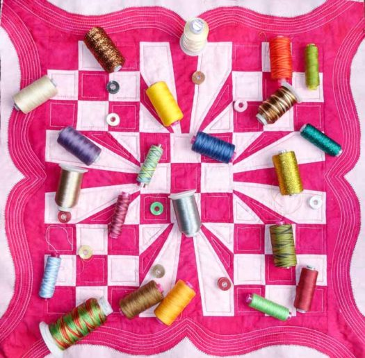 The finished quilt with a large variety of the WonderFil threads spread out on top of the quilt. WonderFil DecoBob Prewound Bobbins.