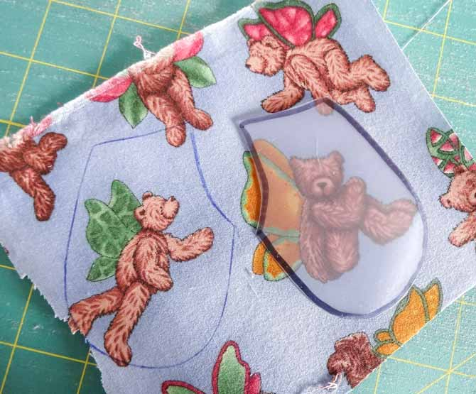 The HEIRLOOM template plastic allows you to see through it. By turning it over you can get a mirror image to the shape you are using.The plastic template is placed on the right side of the fabric and then traced to make the bear's vet.