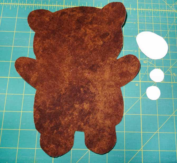 The HEATNBOND sections of the bear have been fused to the wrong side of the fabrics and cut out and are now ready to be fused together
