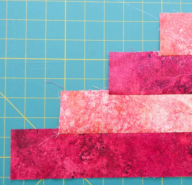 Four strips of fabric which are all the same width are sewn together in a step-wise fashion to reduce fabric waste when cutting the triangles.