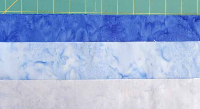 Three blue fabrics with different values will be used to make the 3D blocks with the SEW EASY Half Diamond Ruler.