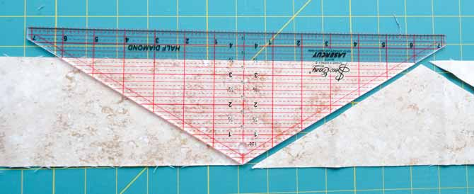 The Half Diamond ruler is plave on the strip of fabric and rotated as pieces are cut and that more are needed.