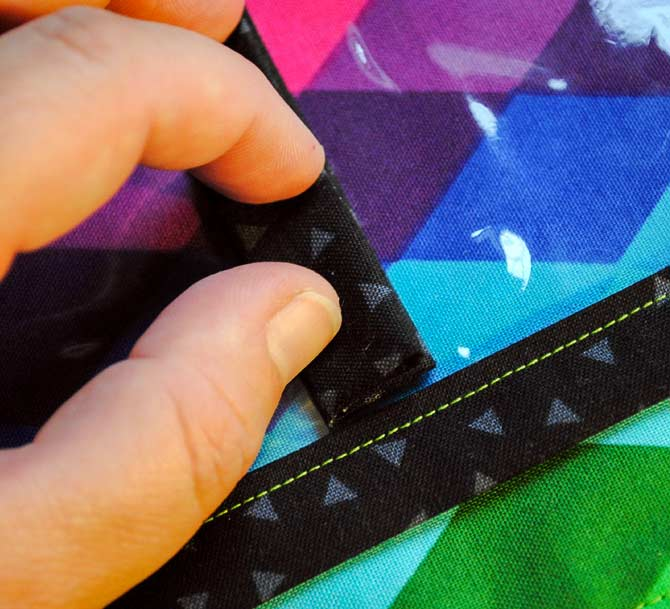 Place the black divider strip along the drawn line and topstitch through all of the layers