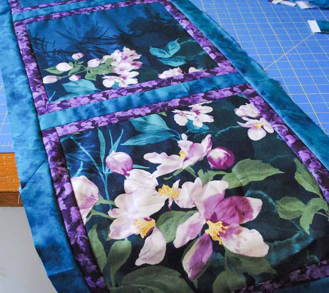 Squares of fabric bordered in purple strips and teal sashing