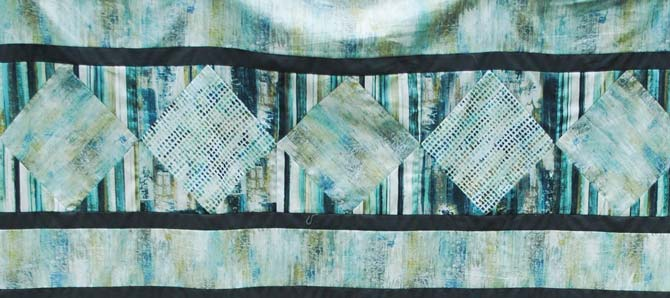 """The top of the Northcott City Scene quilt is composed of the pieced rows, sashing strips and 4"""" strips of fabric."""
