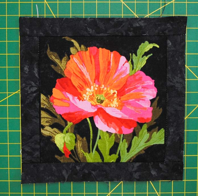 The top and bottom borders are added to the Northcott Full Bloom squares after the side borders are sewn on.