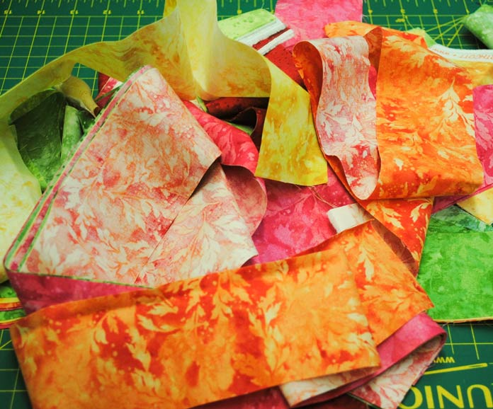 "A pile of colorful 2½"" strips cut from the Full Bloom fabric from Northcott."