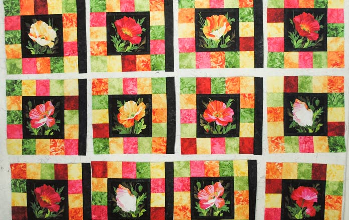 A black sashing strip is sewn to the right side of 15 of the quilt blocks then they are arranged in 5 rows of 4 blocks each.
