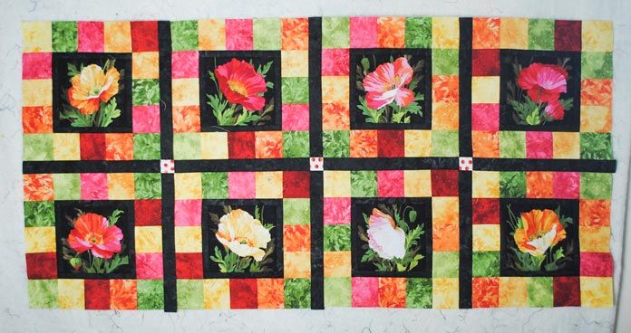 The first two rows of blocks made with the Full Bloom fabric from Northcott are sewn together with a sashing row in between.