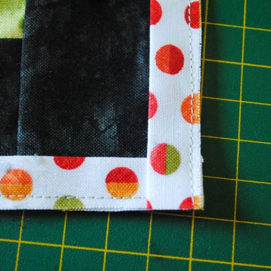 The flange accent strips are overlapped on the corners of the quilt made with the Full Bloom fabric from Northcott.