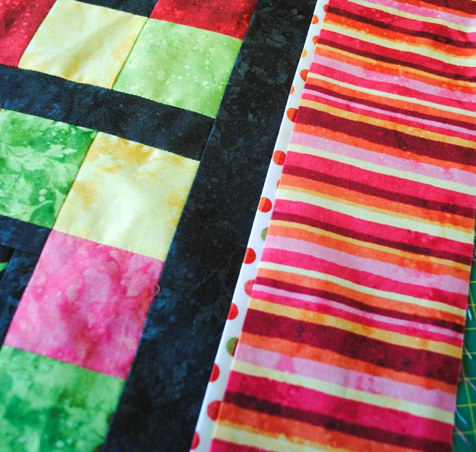 The striped border is pressed away from the middle of the quilt and the flange accent strip is pressed towards the middle.