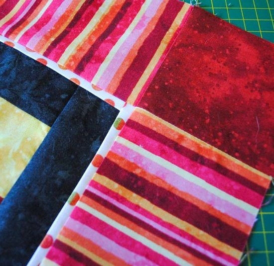 A cornerstone of red fabric is added to each corner of the border to eliminate the need for mitering the corners of the striped Full Bloom fabric.