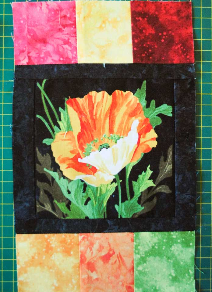 The three section strip sets of Northcott Full Bloom fabric are sewn first to the top and bottom of the square.