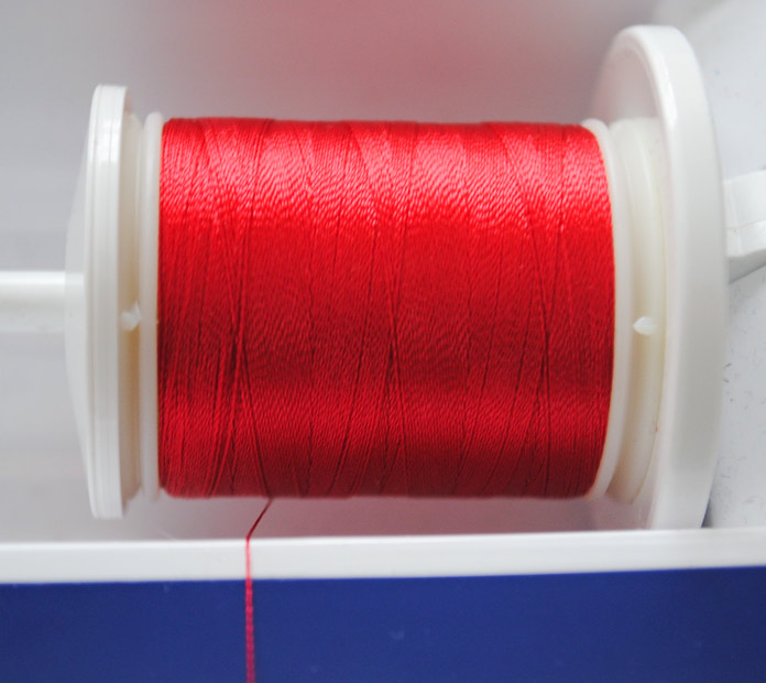 The thread unwinds from the front (bottom) of the spool.