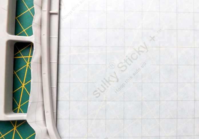 The Sulky Sticky + is labeled so that you know which side to hoop facing up before embroidering with the Dreamweaver XE. A tutorial on how to make quilt labels using machine embroidery and ribbons.