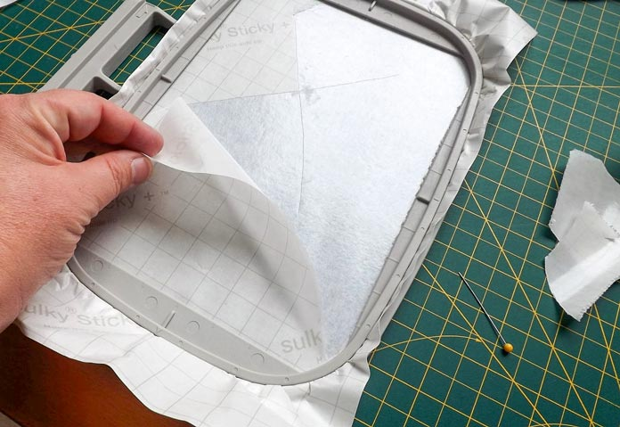 Remove the paper from the stabilizer, exposing the sticky side of the Sulky Sticky +. A tutorial on how to make quilt labels using machine embroidery and ribbons using the Brother Dreamweaver XE